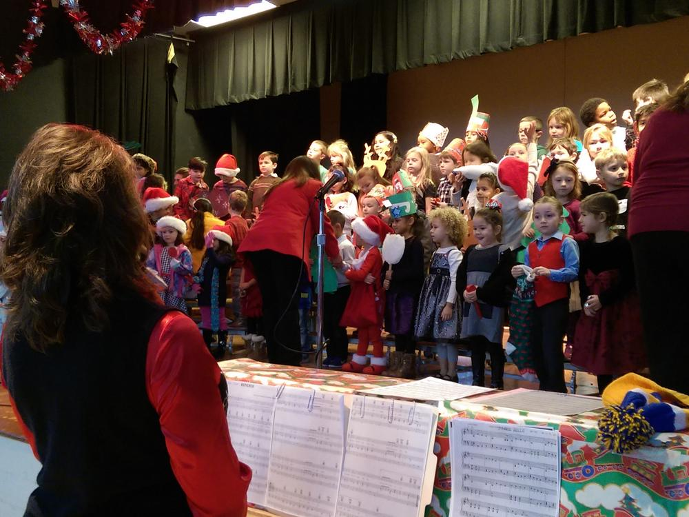 Mrs. Morrow leads the Kindergarten students in a carol at the 2015 Holiday  Concert.